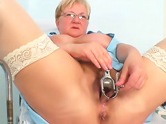 Metal speculum enters mature nurse pussy